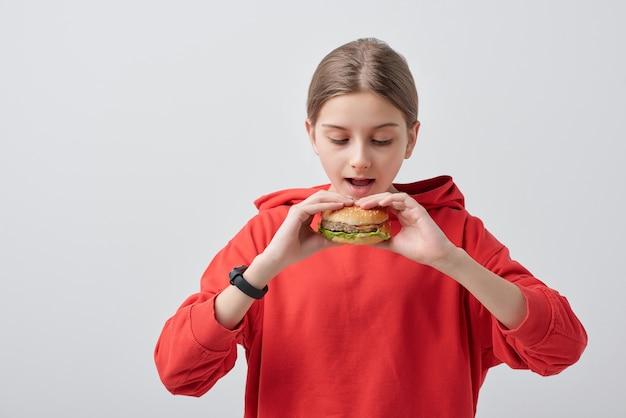 Młodzieńcza dziewczyna w czerwonej bluzie z kapturem, trzymając apetyczny hamburger przy otwartych ustach, jadąc go na białym tle w izolacji