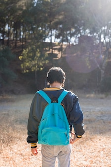 Młodzieńczy chudy facet stoi w parku