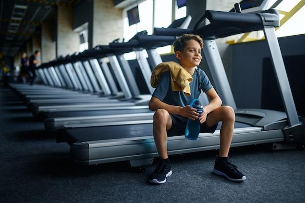 Młodzieniec z wodą siedzi na bieżni w siłowni, uruchomiona maszyna. chłopiec na treningu w klubie sportowym, ochronie zdrowia i zdrowym stylu życia, uczeń na treningu