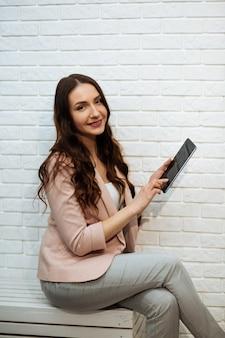 Młodzież i technologia. kolorowy pracowniany portret młoda atrakcyjna brunetka używać pastylka komputer