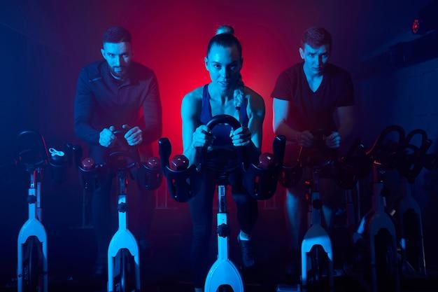 Młodzież na siłowni, ćwicząca nogi, wykonująca trening cardio, trenująca spinning na siłowni w ciemnej, oświetlonej neonami zadymionej przestrzeni