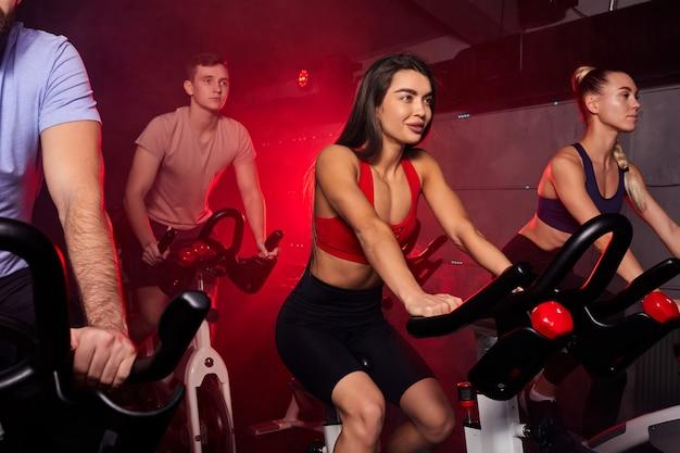 Młodzież na siłowni, doskonale ukształtowani muskularni ludzie trenujący na rowerze, trening cardio na siłowni fitness, przyjmujący odchudzanie na maszynie