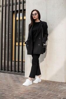 Młodzieżowy strój na co dzień dla kobiet. modna młoda ładna kobieta w czarnej koszulce w pięknej eleganckiej czarnej stylowej marynarce z modną torebką w pobliżu ściany na ulicy. czarny styl.