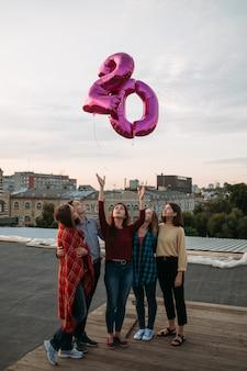 Młodzieżowy styl życia obchody 20. urodzin na dachu. niekonwencjonalna impreza. szczęście wolność i beztroska. balony latają