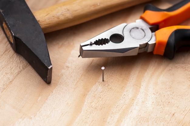 Młot, gwoździe i szczypce leżą na drewnianym tle. narzędzia budowlane selektywne ustawianie ostrości