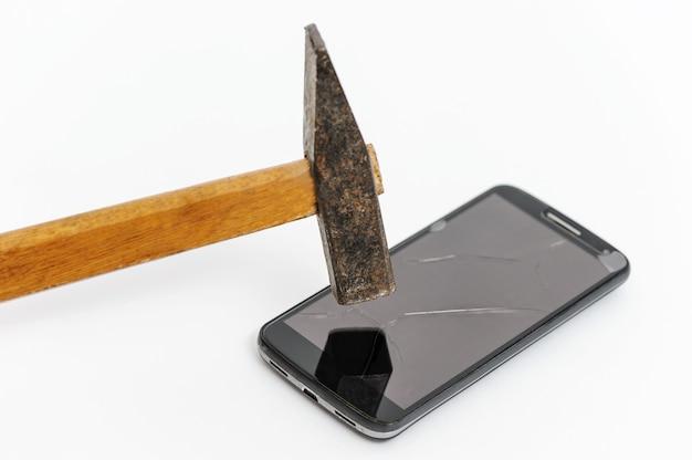 Młot rozbija ekran smartfona.