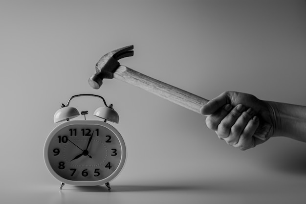 Młot walczy o zniszczenie budzika. koncepcja walki i limitów czasowych.