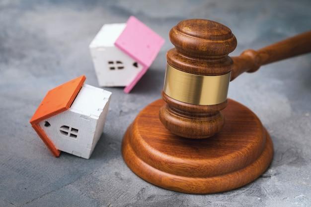 Młotek aukcyjny i przewrócone domy z zabawkami na stole, koncepcja sprzedaży nieruchomości