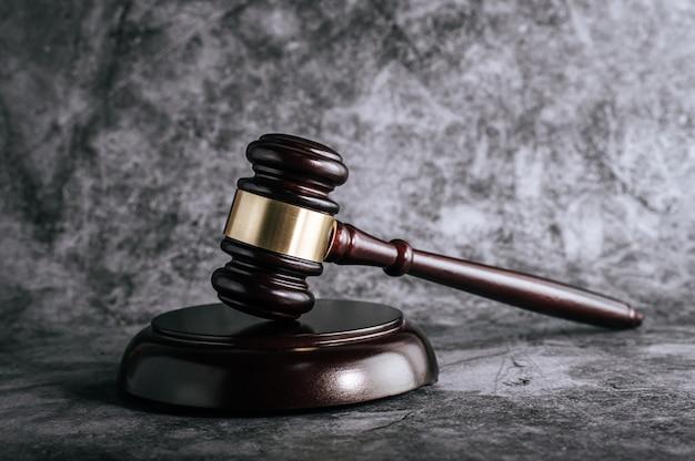Młotek drewniany sędziów na stole w sali sądowej lub w biurze egzekucyjnym.