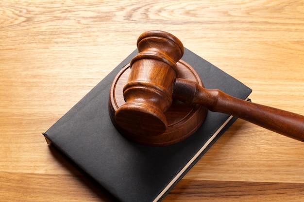 Młotek i legalna książka na drewnianym stole