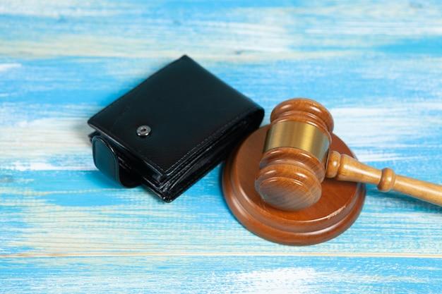 Młotek i portfel na stole przekupstwo władz lub ograniczenia dochodów finansowych