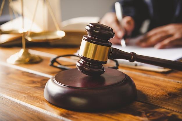 Młotek i sędzia podpisujący dokumenty