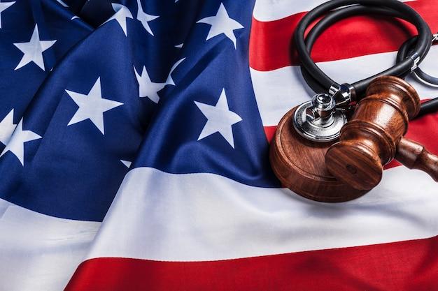 Młotek i stetoskop na flagi narodowej usa. koncepcja medycyny sądowej. sądowa praktyka lekarska