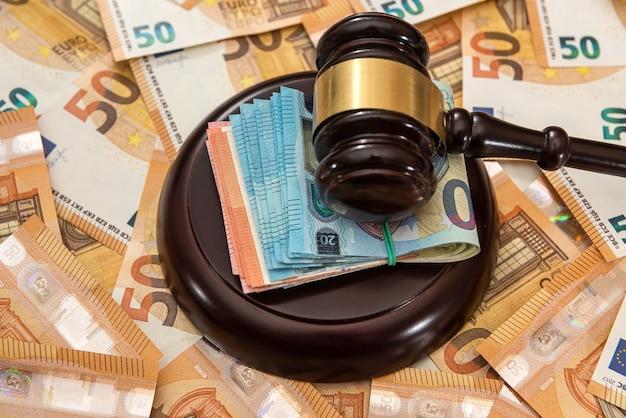Młotek i wiele banknotów 50 euro. koncepcja korupcji i łapówkarstwa