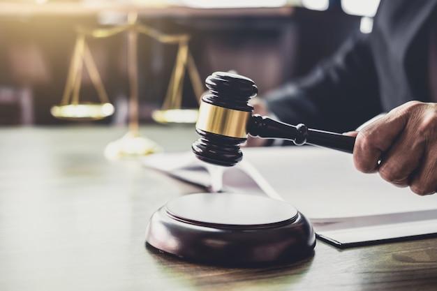 Młotek na drewnianym stole i doradca lub mężczyzna prawnik pracuje na dokumenty. prawo prawne