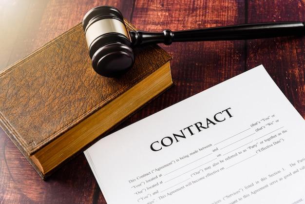 Młotek na książki prawa, które regulują umowy papierowe do prowadzenia działalności gospodarczej.
