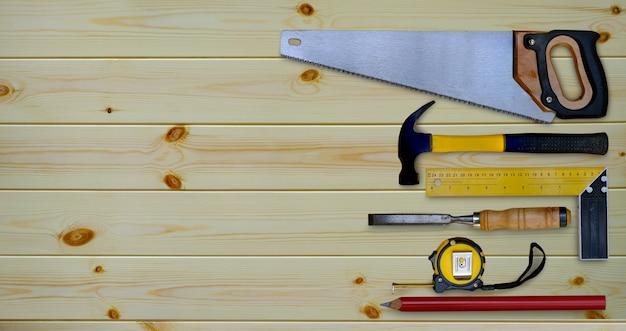 Młotek piła taśma miernicza wypróbuj kwadratowy ołówek i dłuto kolekcję narzędzi ręcznych do obróbki drewna na drewnianym stole warsztatowym