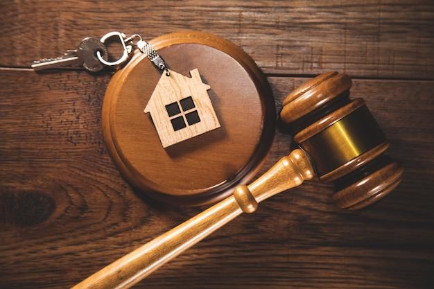 Młotek sędziego i klucz do domu na szarym tle. pojęcie prawa nieruchomości