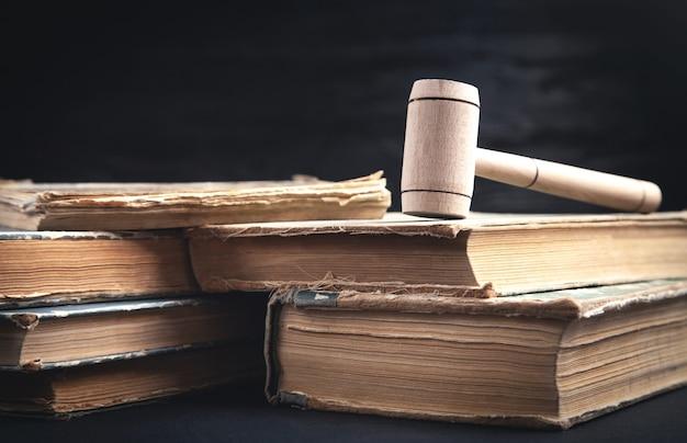 Młotek sędziego i książka na czarnym tle.