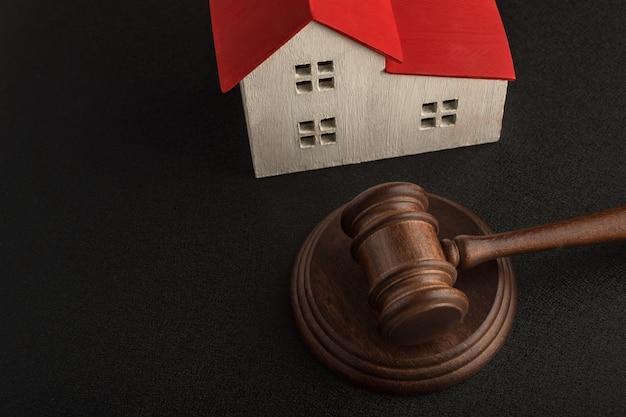 Młotek sędziego i model domu na czarnej przestrzeni. aukcja nieruchomości. skonfiskowane mieszkania. rozwiązywanie sporów majątkowych