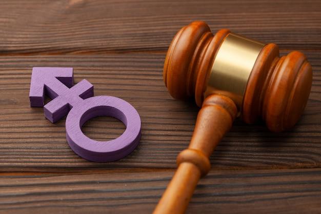 Młotek sędziego i symbol płci transpłciowej.