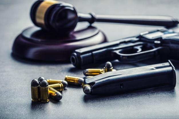 Młotek sędziego. sprawiedliwość i broń. sprawiedliwość i wymiar sprawiedliwości w bezprawnym użyciu broni. wyrok w morderstwie.