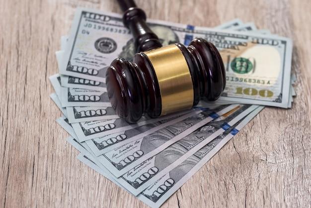 Młotek sędziego z amerykańskimi dolarami na drewnianym stole