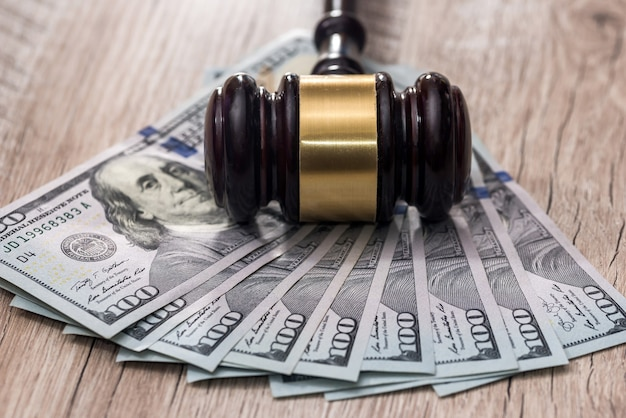 Młotek sędziego z dolarami amerykańskimi na drewnianym stole