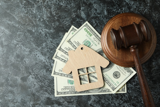 Młotek sędziowski, dolary i drewniany dom na czarnym smokey stole