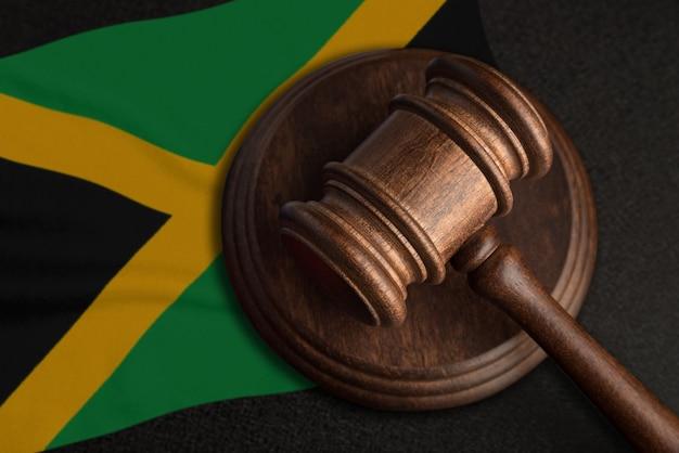 Młotek sędziowski i flaga jamajki. prawo i sprawiedliwość na jamajce. naruszenie praw i wolności.