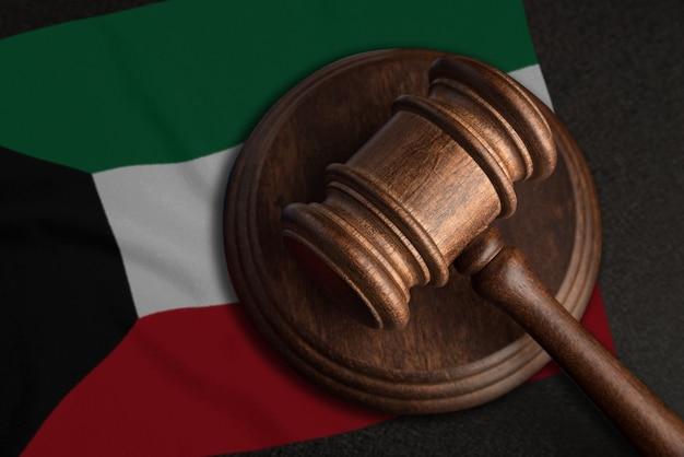 Młotek sędziowski i flaga kuwejtu. prawo i sprawiedliwość w kuwejcie. naruszenie praw i wolności.