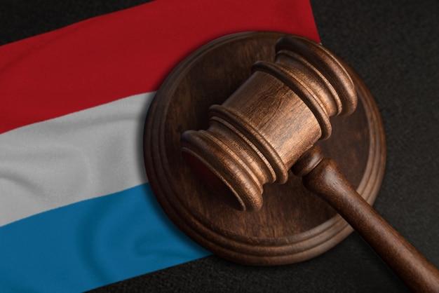 Młotek sędziowski i flaga luksemburga. prawo i sprawiedliwość w luksemburgu. naruszenie praw i wolności.
