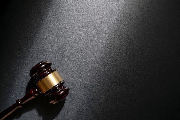 Młotek sędziowski na czarnym skórzanym tle, widok z góry. pojęcie prawa.