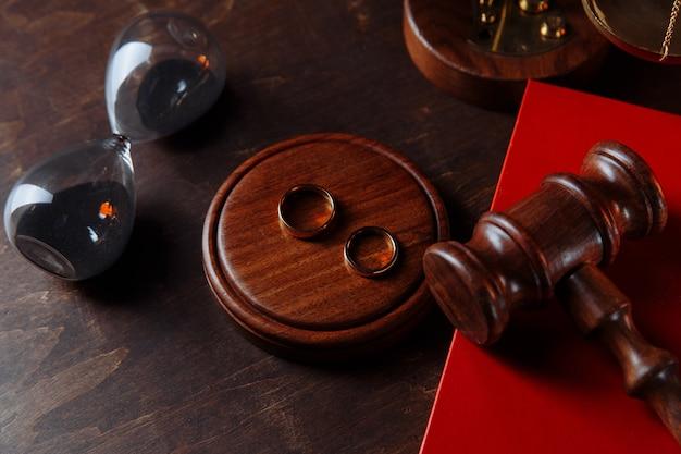 Młotek sędziowski na książeczce i pierścieniach. pojęcie rozwodu