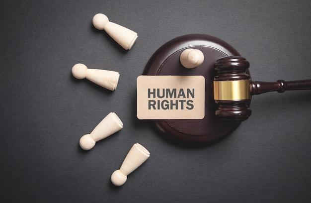 Młotek sędziowski z drewnianymi figurami ludzkimi. prawa człowieka
