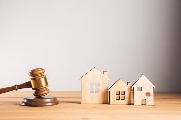 Młotek sędziowski z modelami drewnianych domów na stole