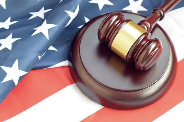 Młotek sprawiedliwości na flagę stanów zjednoczonych w sali sądowej podczas procesu sądowego