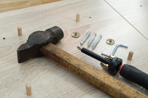 Młotek, śrubokręt, specjalne wkręty meblowe i śrubokręt znajdują się na elementach meblowych z płyty wiórowej