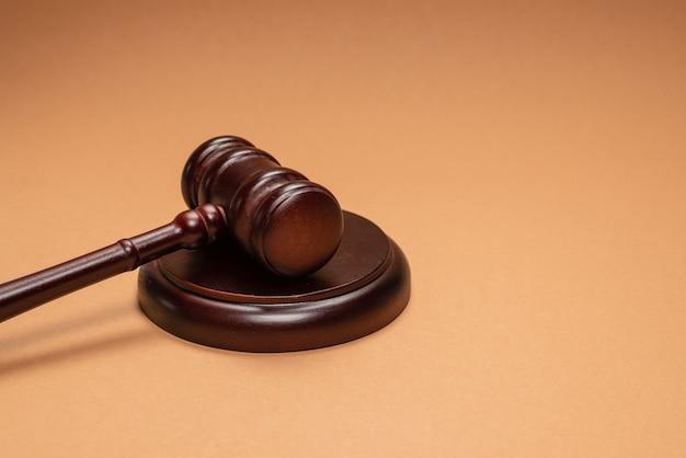 Młotek w dół na stojaku na brązowym tle. konceptualny system sprawiedliwości prawa. skopiuj miejsce.