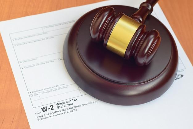 Młotek wymiaru sprawiedliwości i formularz deklaracji płac i podatków w-2 z urzędu skarbowego