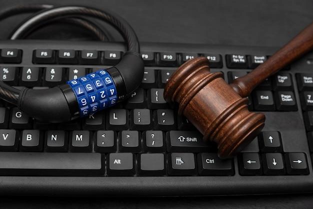 Młotek z zamkiem szyfrowym na klawiaturze komputera. koncepcja ochrony danych.