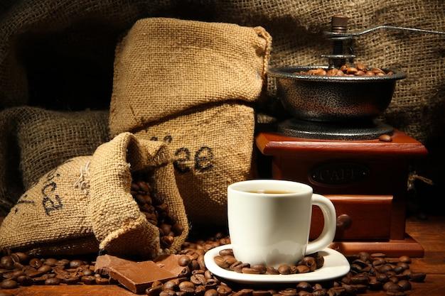 Młynek do kawy i filiżanka kawy na ścianie z juty