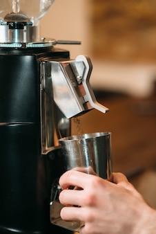 Młynek do kawy napełnia filiżankę kawą.