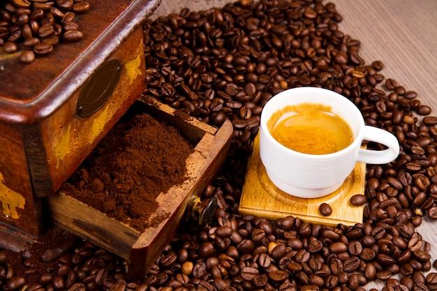 Młynek do kawy z fasolą i filiżanką kawy