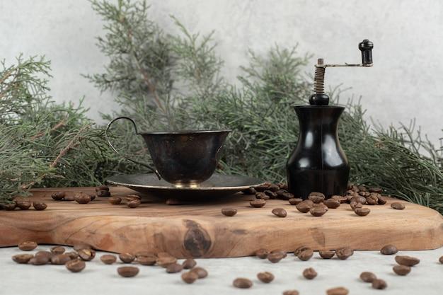 Młynek do kawy, ziarna i aromatyczna kawa na drewnianej desce