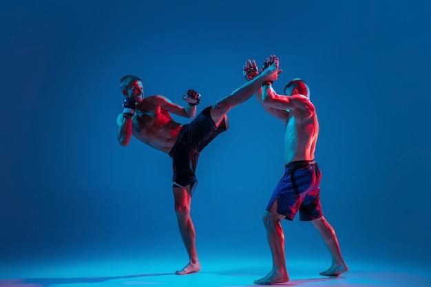 Mma. dwóch zawodowych wojowników uderzających lub boksujących na białym tle na niebieskiej ścianie w neonie