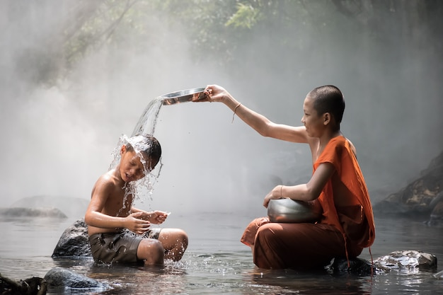 Mnich i chłopiec bawi się w wodę