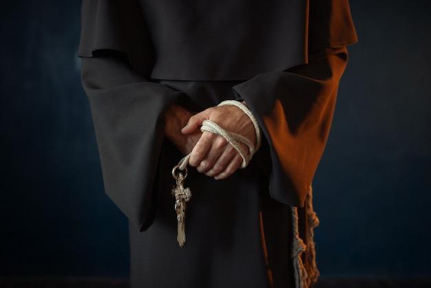 Mnich trzyma w rękach drewniany różaniec i krzyż
