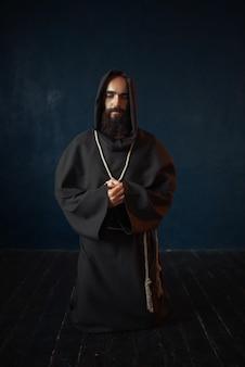 Mnich w czarnej szacie z kapturem klęczący i modlący się, religia. tajemniczy zakonnik w ciemnej pelerynie