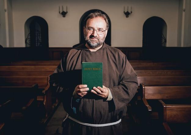 Mnich w szatach ze świętą biblią w rękach modli się w kościele